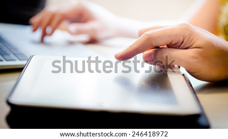 Hand Touching Screen On Modern Digital Tablet PC. Selective focus on finger. With Hand Playing Laptop In Background - stock photo