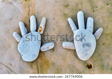 Hand trace of pebbles on the sea boulder - stock photo