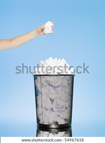 Hand trowing a paper into a wastebasket on blue background - stock photo