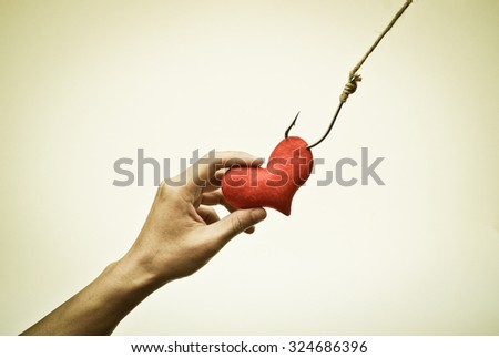 hand trying to catch a red heart on a fish hook - Love trap concept