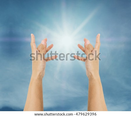 Hand trying to reach on the sky with sun rays