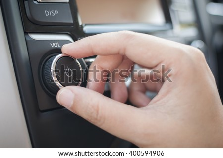 Hand tuning fm radio button in car panel. - stock photo