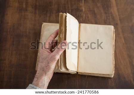 Hand turning blank pages of a vintage book. Shallow depth of field with focus on thumb, fingers and page edges. - stock photo