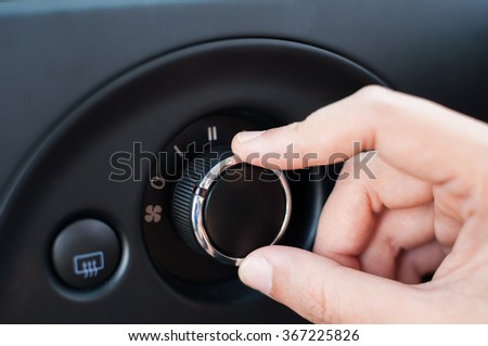 Hand turning dial button of air condition fan control panel.  - stock photo