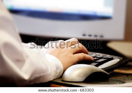 Hand typing on computer keyboard with mouse and monitor- represents computer work at office/school/home, and/or surfing the internet. - stock photo