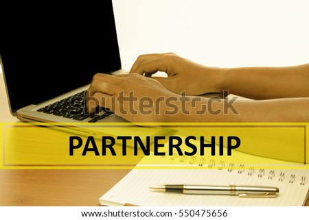 Hand Typing on keyboard with text PARTNERSHIP