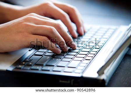 hand typing on laptop keyboard - stock photo