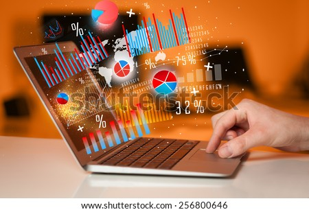 Hand typing on modern laptop notebook computer with future graph icons and symbols  - stock photo