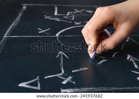 Hand under blackboard with scheme football game, closeup - stock photo