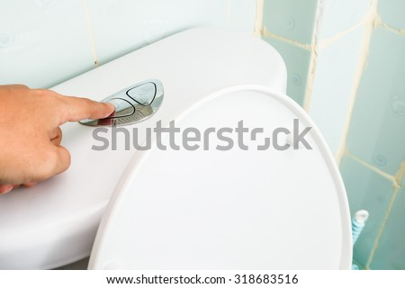 Hand use flush cleaning toilet - stock photo