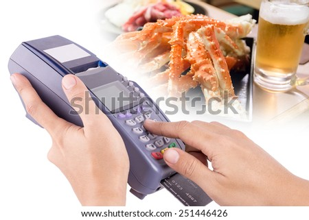 Hand Using Credit Card Machin with Food in Background For Your Restaurant Business - stock photo