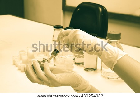 hand using hypodermic syringe to liquid in glass bottle with chemical bottle on table background - stock photo