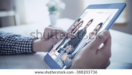 Hand using tablet against portrait of a positive team sitting at a table - stock photo