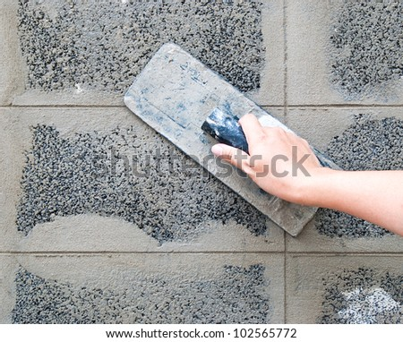 Hand using trowel - stock photo