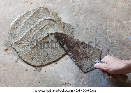 hand using trowel  with wet concrete floor - stock photo