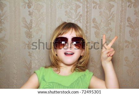 hand victory gesture little girl funny sunglasses retro wallpaper - stock photo