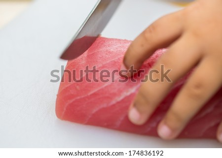 Hand was sliced ??fish to make sushi