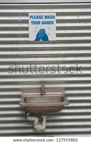 hand washing station mounted against corrugated iron - stock photo