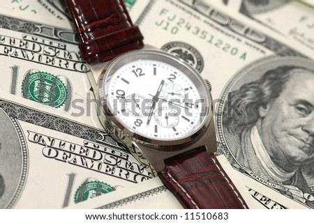 Hand watch over  the hundred dollar bank notes - stock photo