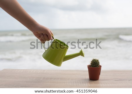 hand watering a cactus with watering-can