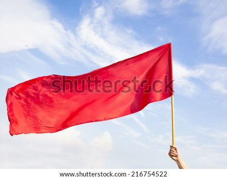Hand waving a red flag with blue sky background - stock photo
