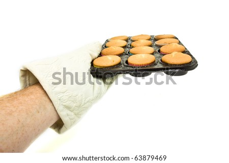 Hand wearing oven mit holding hot tray of freshly cooked cup cakes. - stock photo