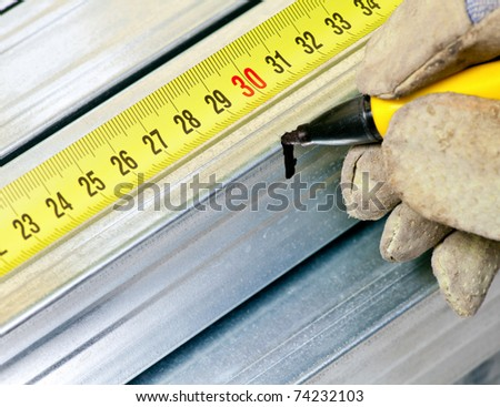 Hand wearing protective glove holding marker pen marking measurement on a metal stud - stock photo