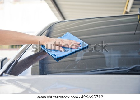 Hand wipe cleaning the car with blue microfiber cloth