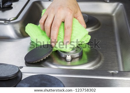 Hand wiping clean stove top and burner covers with green microfiber cloth - stock photo