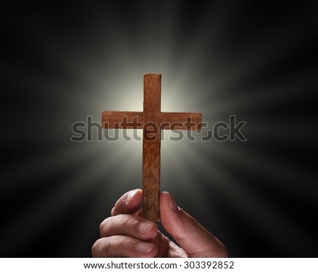 Hand with a cross against dark background, religious concept - stock photo