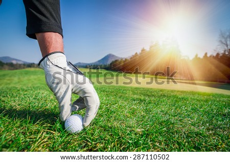 Hand with a glove is placing a t golf ball on the ground. Golf course with green grass with mountains in the background. Soft focus or shallow depth of field. Sunshine in the background - stock photo