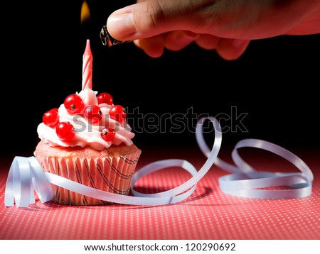 hand with a  lighter to light the candle blueberry muffins blue ribbon red white dotted red table and black background