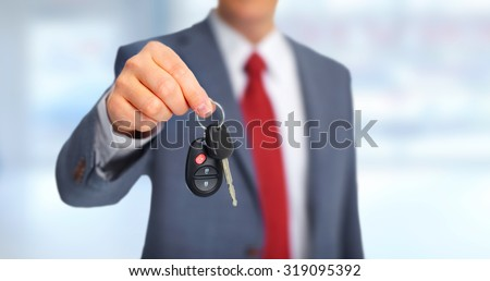 Hand with a new Car keys over garage background. - stock photo
