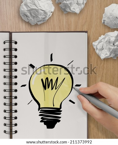 hand with a pen drawing light bulb on note book as concept - stock photo