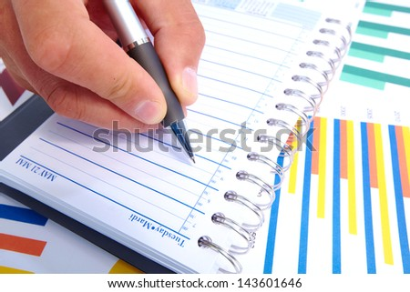 Hand with a pen. Finance and accounting business background.