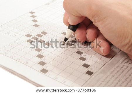 Hand with a pen writing on a crossword puzzle - stock photo