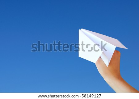 Hand with a plane on the sky background - stock photo