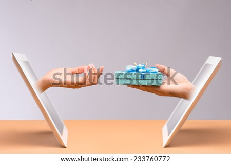 Hand with a present coming out of digital tablet - stock photo
