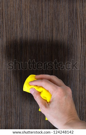 dusting wood furniture. hand with a rag to dust the wood furniture vertical image dusting