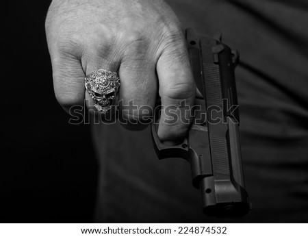 Hand with a ring in the form of a skull holding a handgun, close up (black white) - stock photo