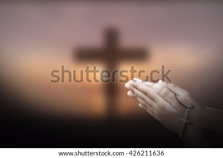 Hand with a rosary against cross background, religious concept. - stock photo
