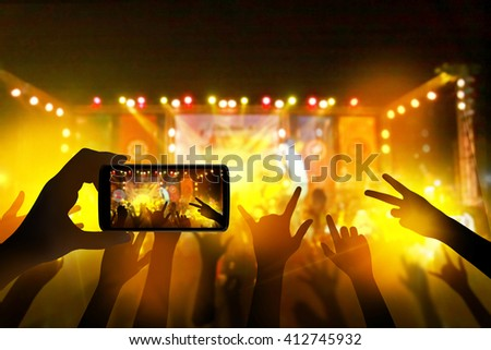 Hand with a smartphone records live music festival, live concert, music festival, happy youth, luxury party, landscape exterior.  - stock photo