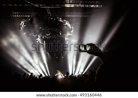 Hand with a smartphone records live music festival, Taking photo of rock concert stage, live concert, music festival, happy youth, luxury party, landscape exterior.