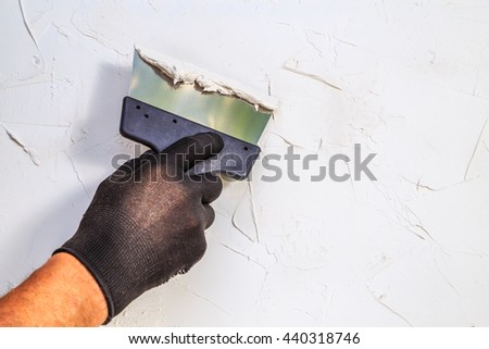 Hand with a spatula. Tools, plaster walls. - stock photo