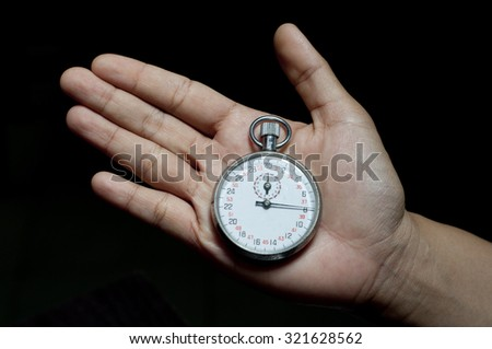 Hand with a stopwatch. Isolated on black background.