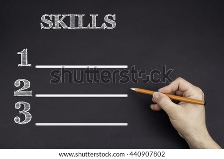 Hand with a white pencil writing: SKILLS blank list