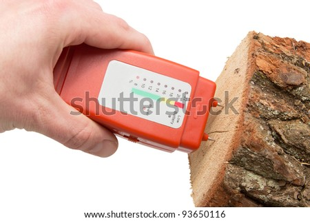 Hand with a wood moisture meter and firewood over a white background - stock photo
