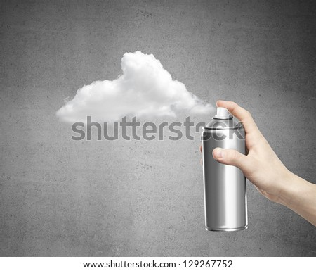 hand with aerosol can on concrete background - stock photo