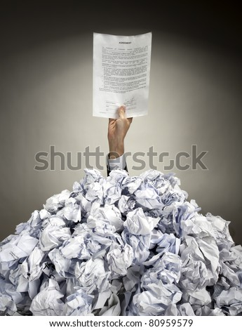 Hand with Agreement reaches out from big heap of crumpled papers - stock photo