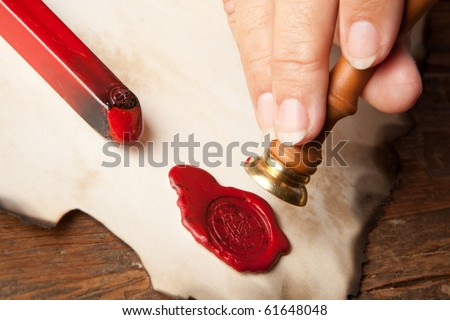 Hand with ancient parchment or diploma scroll with wax seal - stock photo
